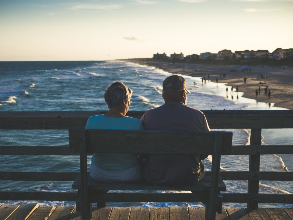 couple sitting on bench on pier