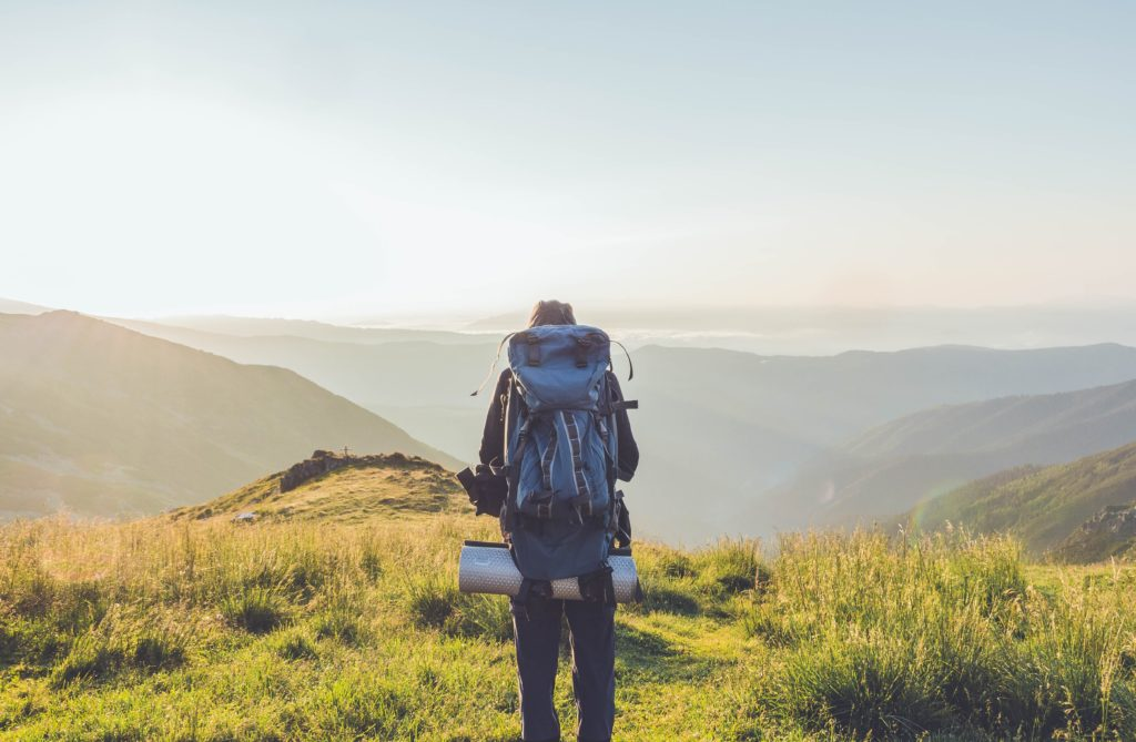 man standing at top of mountains with hiking bag